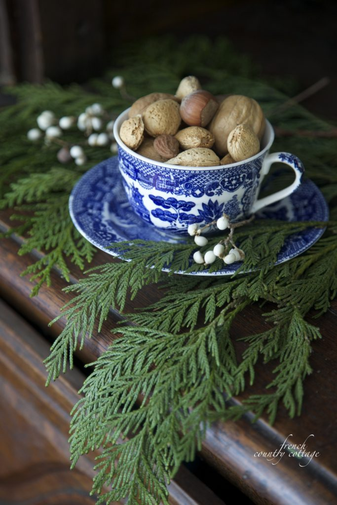 Blue Transferware cup filled with nuts with Christmas greens
