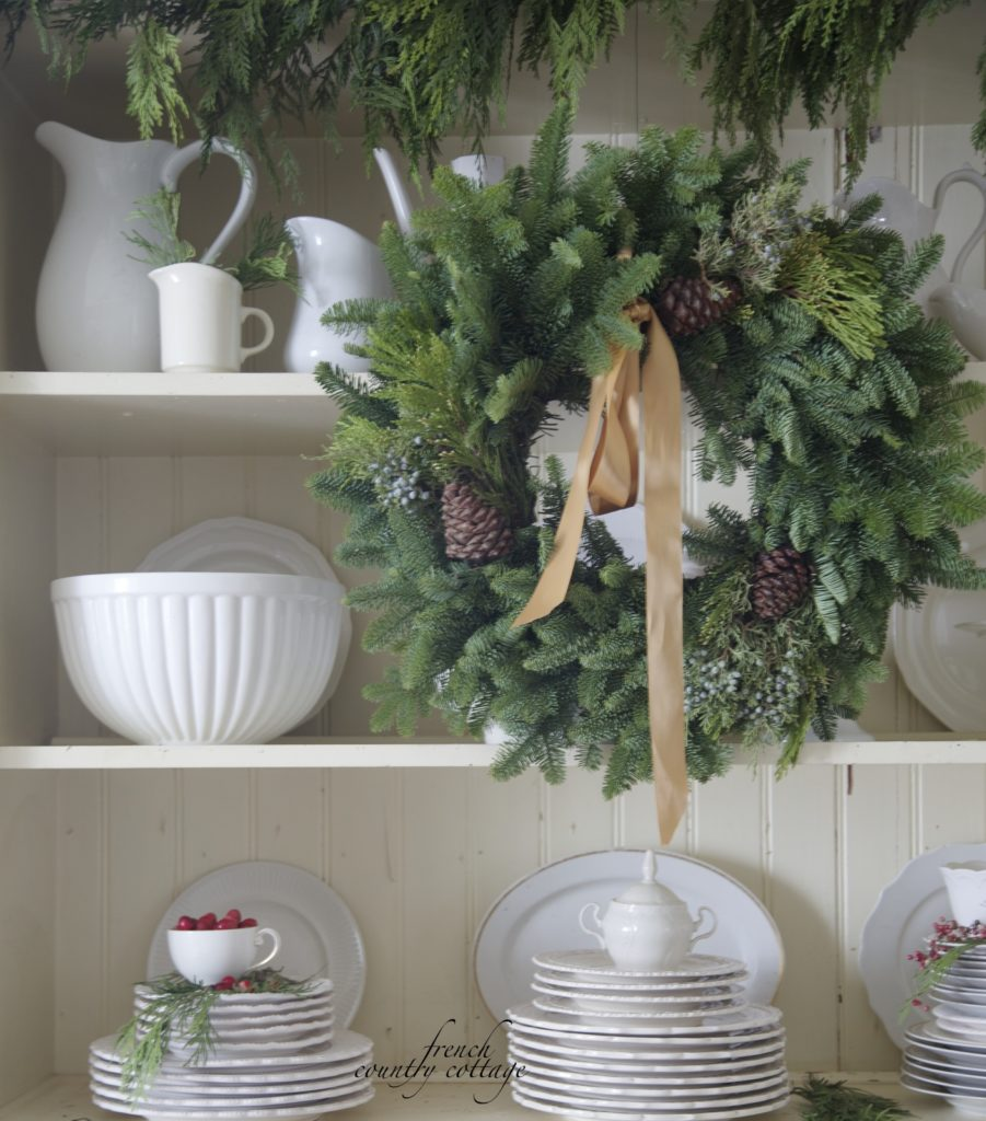 Christmas wreath on cupboard with white dishes