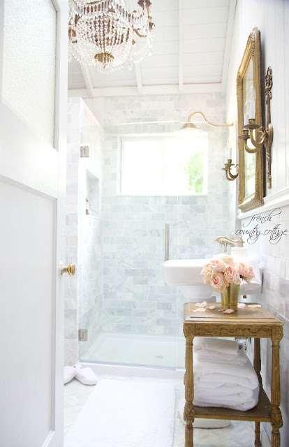 Bathroom makeover with marble subway tile, gold fixtures and vintage