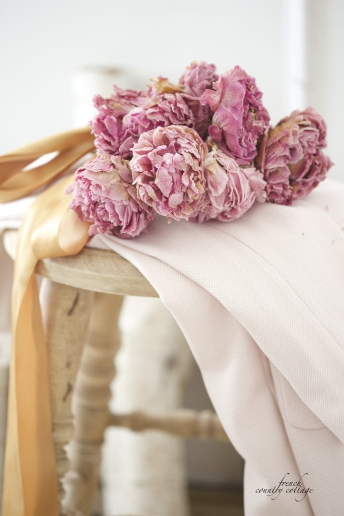 Dried peony bouquet on blush coat on stool