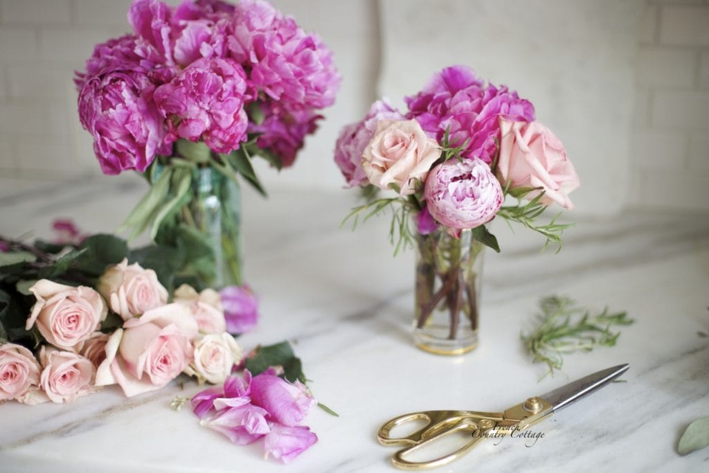 Peonies and roses on marble counter with gold scissors
