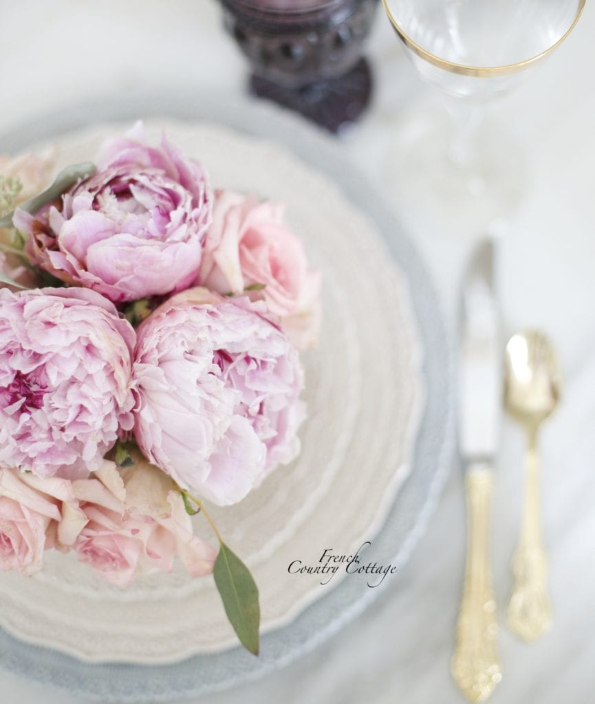 Peonies and roses on lace plates with gold flatware