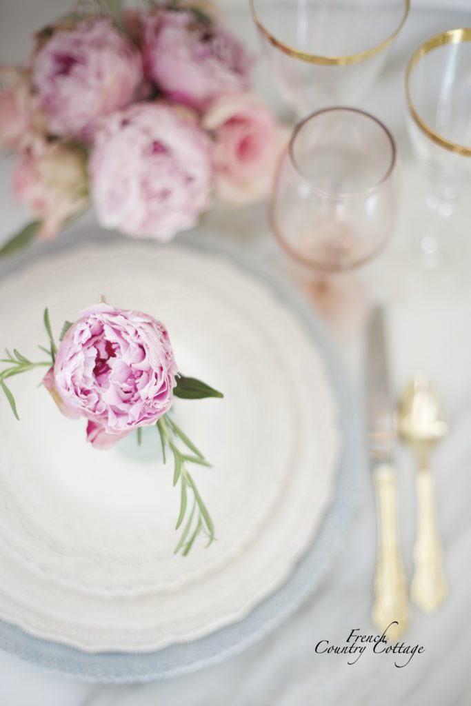 Peony with rosemary in bottle on a plate