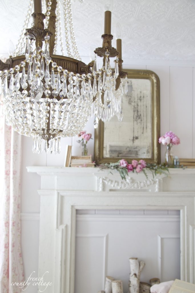 Chandelier with mantel and peonies in background