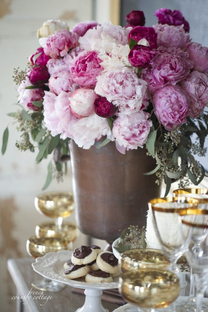 Peonies in a container with gold glasses all around