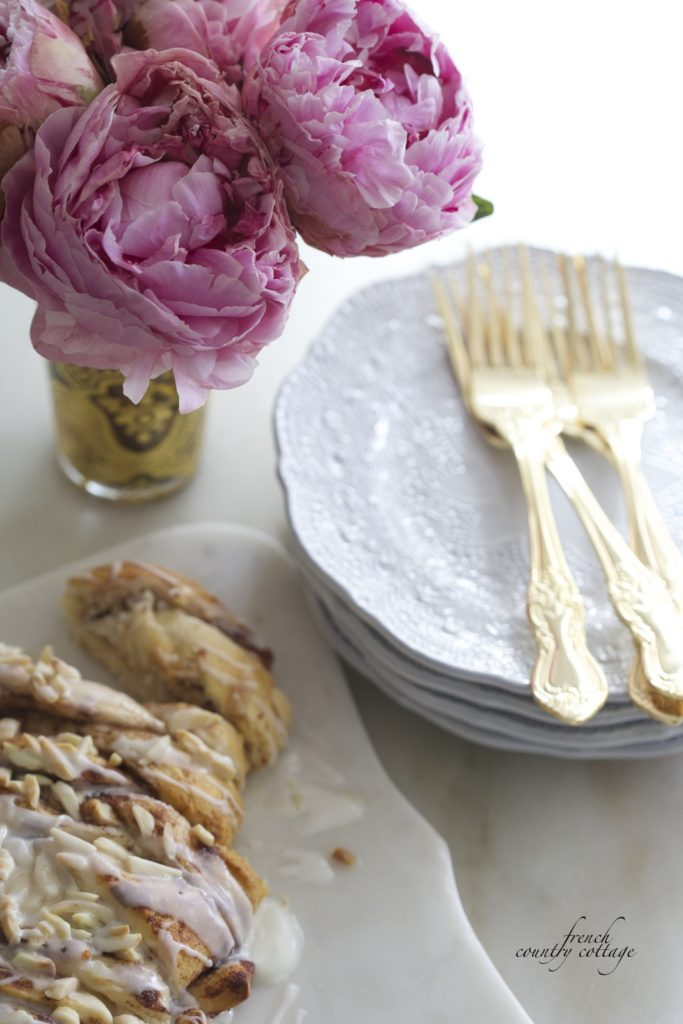 Cinnamon braided bread on counter with dishes and peonies