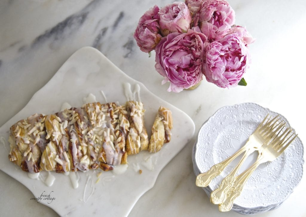 Braided cinnamon roll bread on counter with peonies and dishes