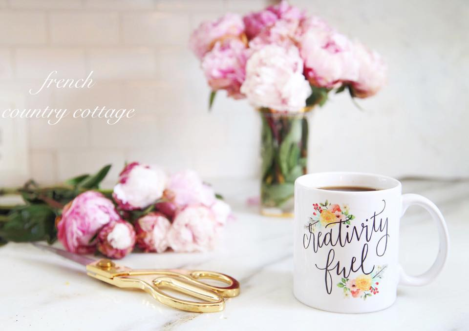 Coffee mug, gold scissors and peonies on the counter