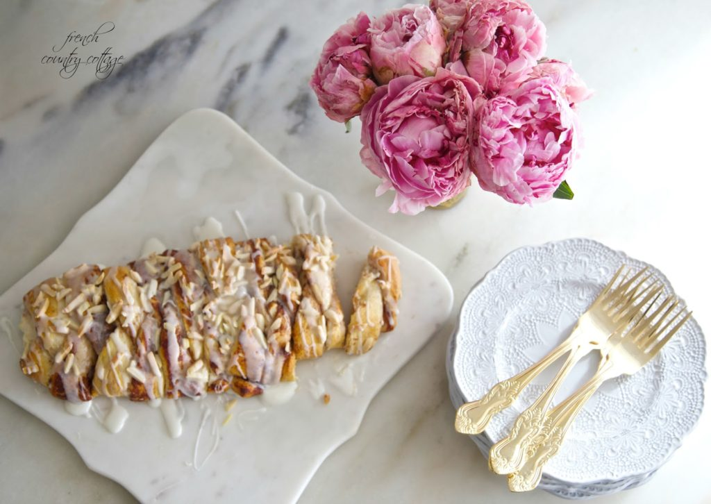 Breakfast pastry with peonies and dishes on marble counter