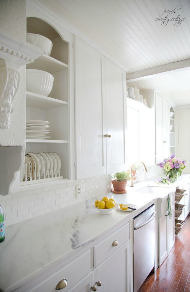 Marble counters in French Cottage kitchen with lemons and flowers and plate rack