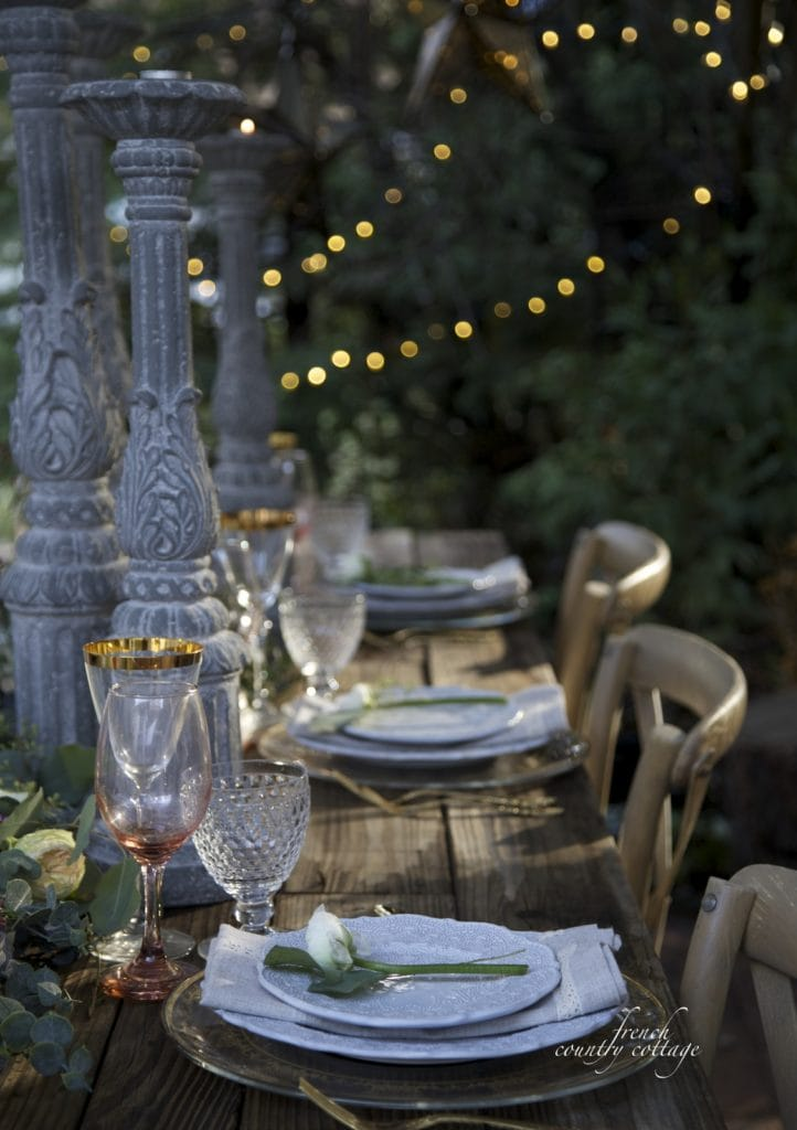 Outdoor table setting with candlesticks and twinkling lights in the trees