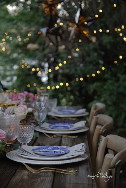 Blue and white dishes with mixed glasses on table and lights twinkling in background