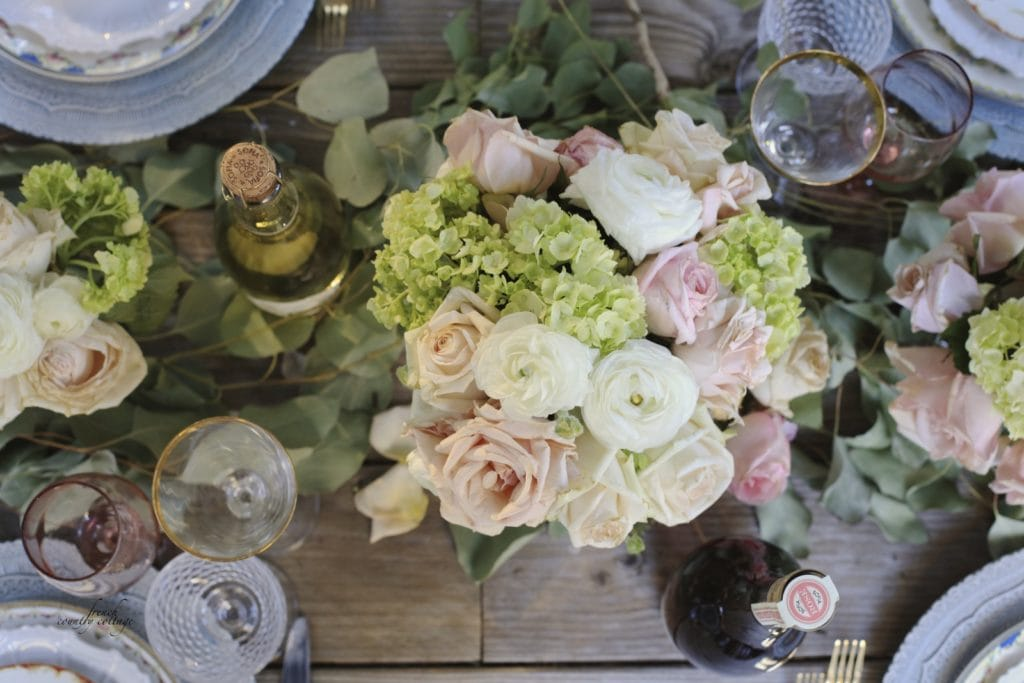 Flowers and place setting elements on rustic tabletop