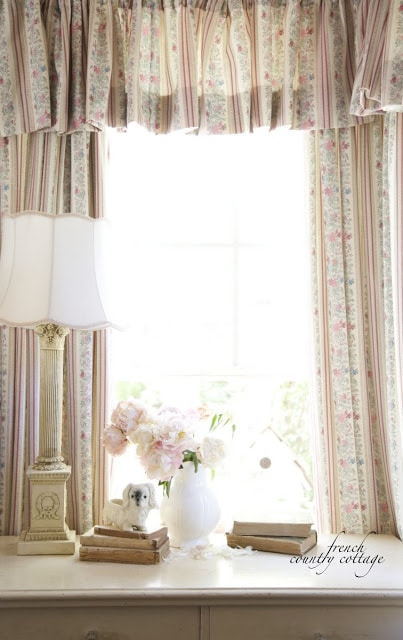 Vintage French flower ticking stripe curtains with lamp and dog statue on nightstand