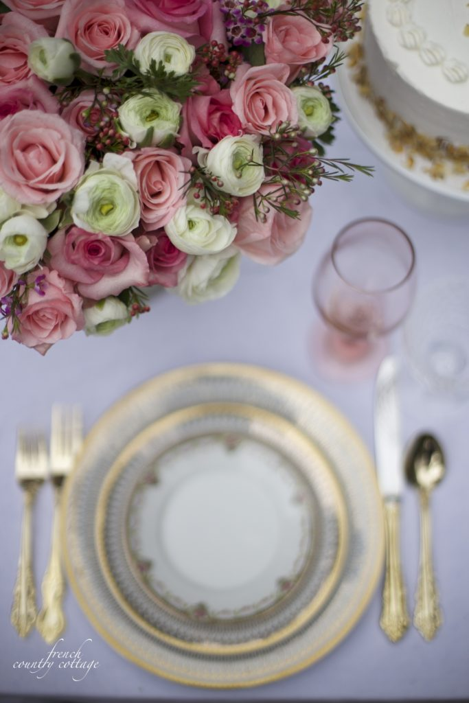 Gold dishes, pink flowers and gold flatware table setting