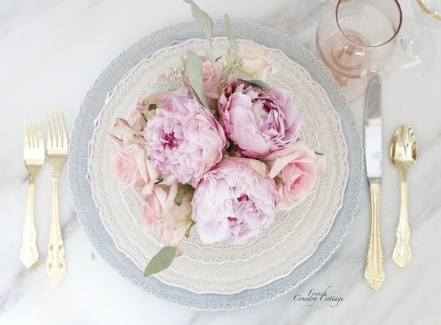 roses and peonies in a place setting bouquet on lacy dishes