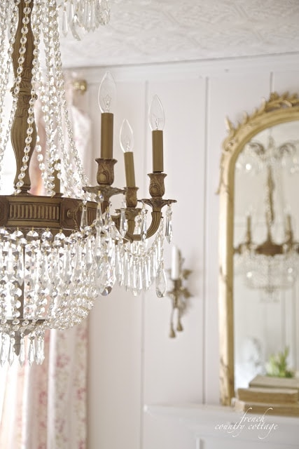 Chandelier and floral fabric panels in background