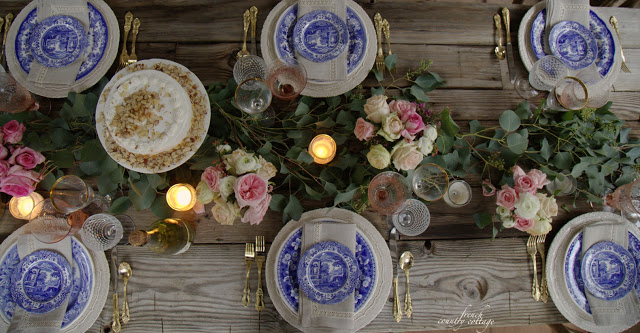 Rustic table with blue and white and flowers marching down the center
