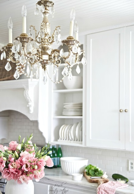 Chandelier and dishes in open shelves in kitchen