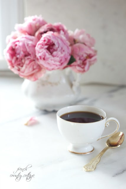 cup of coffee with peonies on marble counter