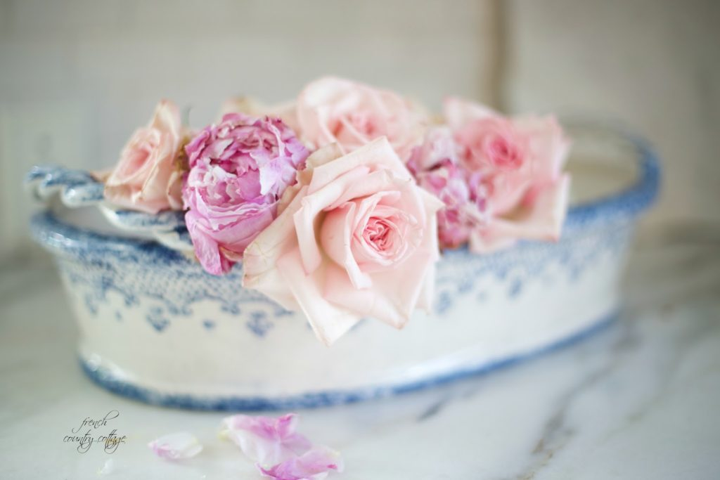 Roses and peonies in blue and white pottery on counter