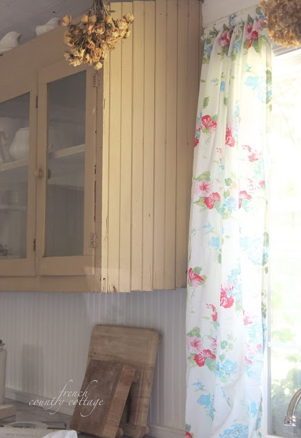 Vintage floral panels on window in cottage kitchen