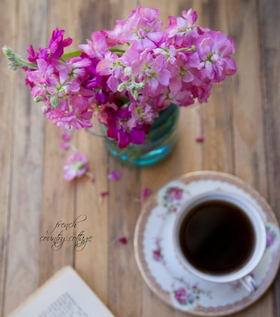 Coffee and flowers on rustic table top with book