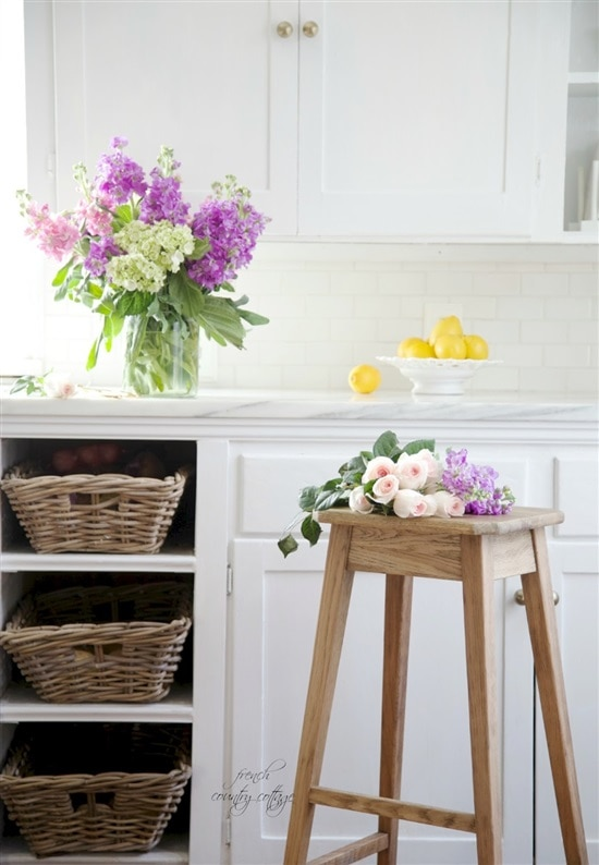 vintage style stool in kitchen with marble counters and flowers