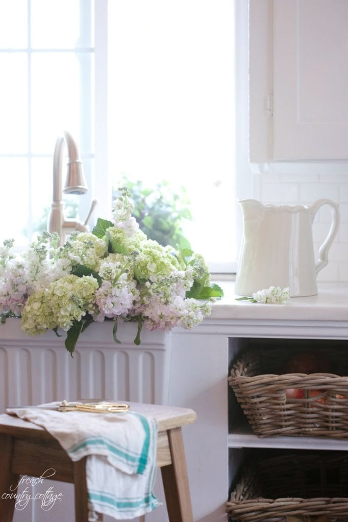 farmhouse sink in kitchen with flowers