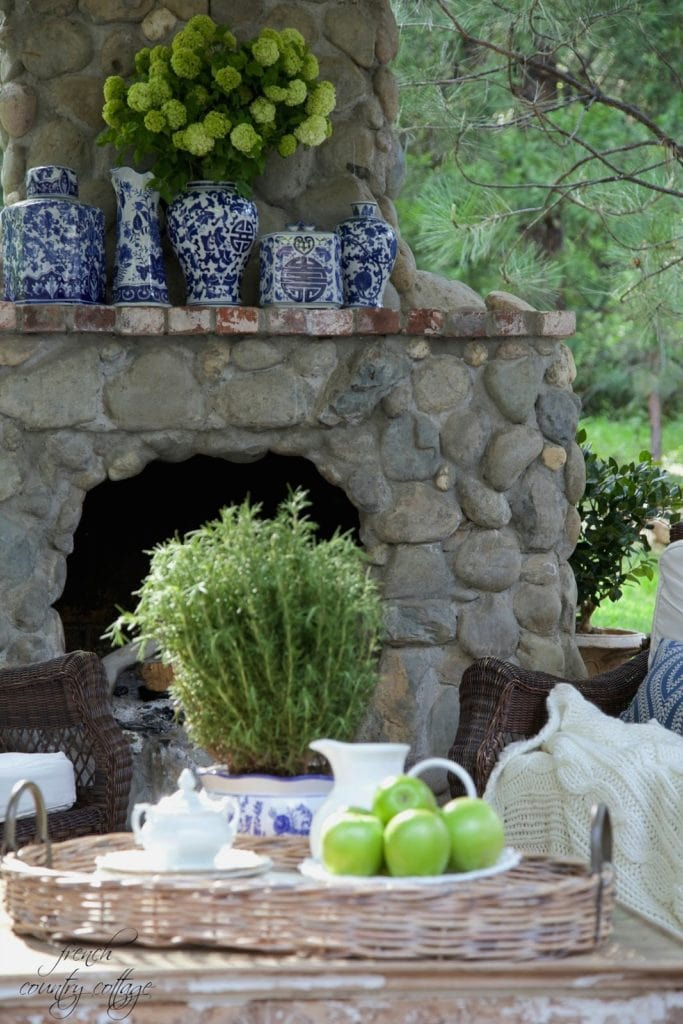 Outdoor rock fireplace with blue and white pottery