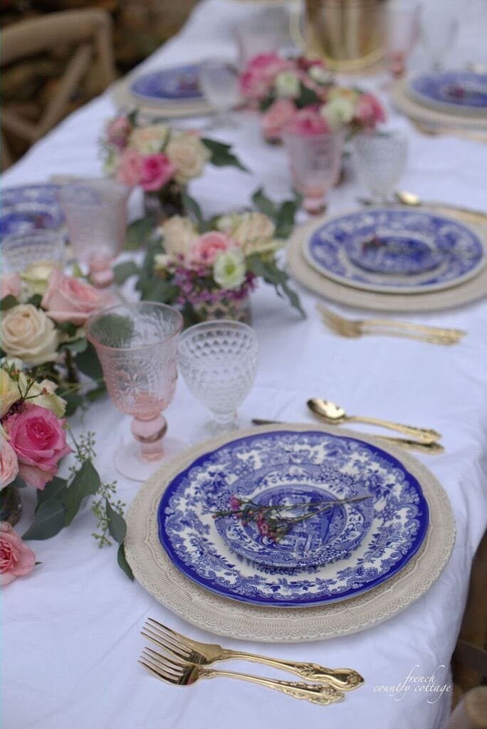 Blue and white table setting with romantic pink and gold accents