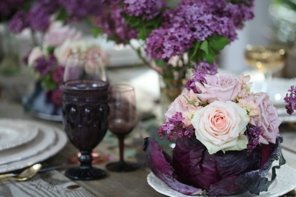 Lilacs and roses on table in cabbage with purple glasses