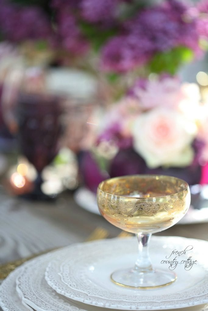 Gold glasses with purple flowers in the background