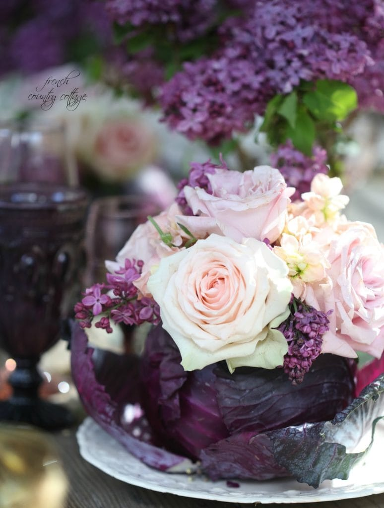 Cabbage turned into vase filled with roses and lilac on table