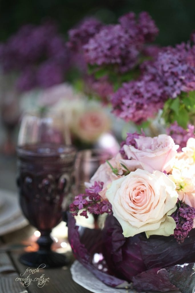 Lilacs and roses in a purple cabbage on table for spring centerpiece