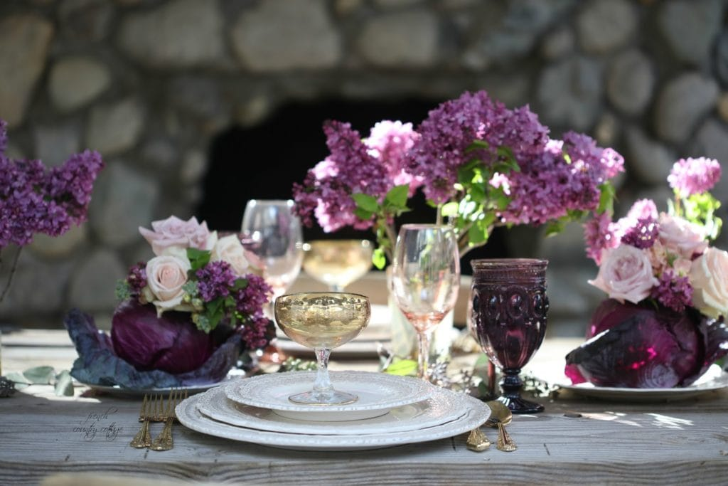 Table with purple flowers and cabbage vase
