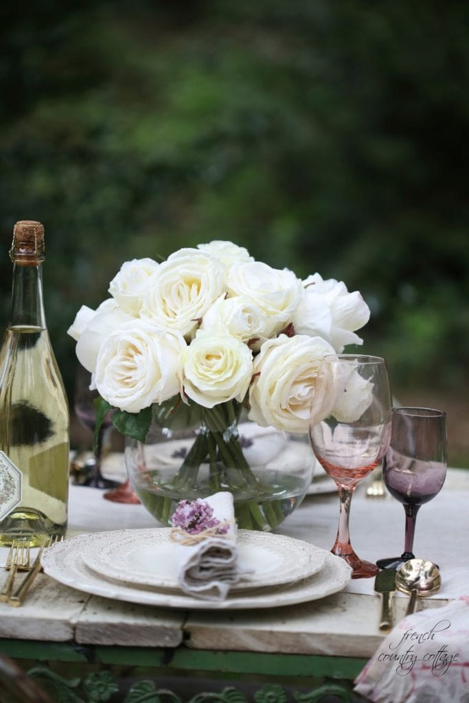 white roses, lilac and gold flatware on vintage table
