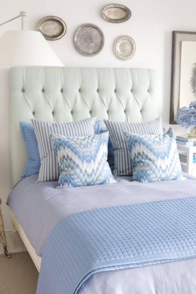 Blue bedroom with silver platters on wall