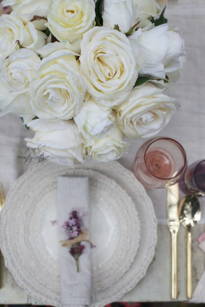 place setting, gold flatware, pink wine glass and roses and lilac