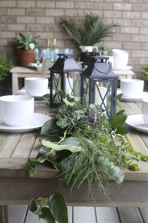 fresh greens and metal lanterns on dining table