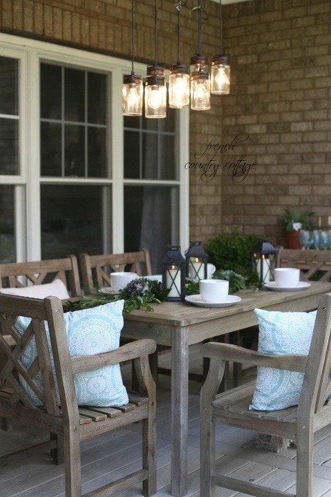 Outdoor dining table with white dishes and lanterns