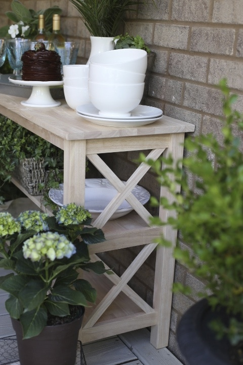 Side table in outdoor dining area with plants and dishes