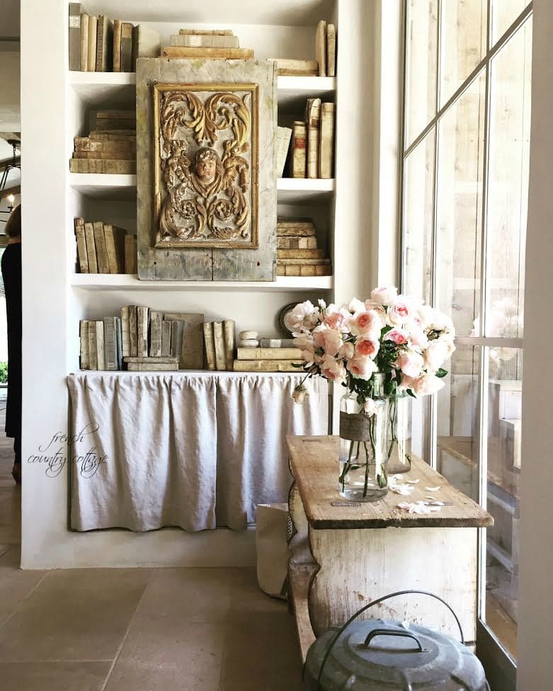 Office area with book shelf filled with books and roses in glass