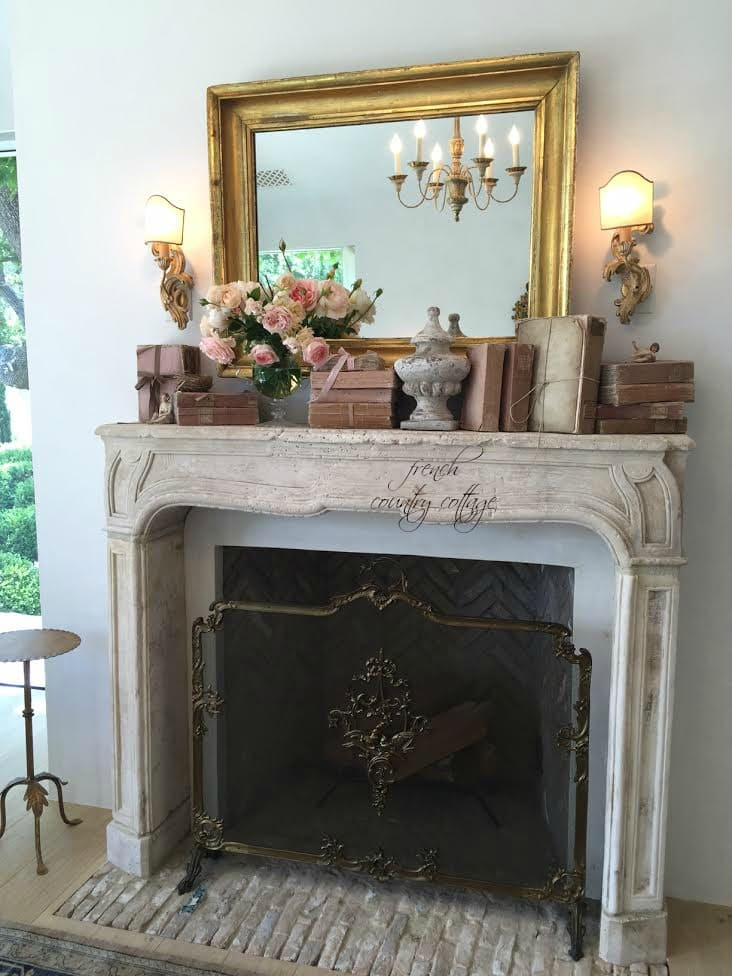 Gold mirror with pink books on fireplace