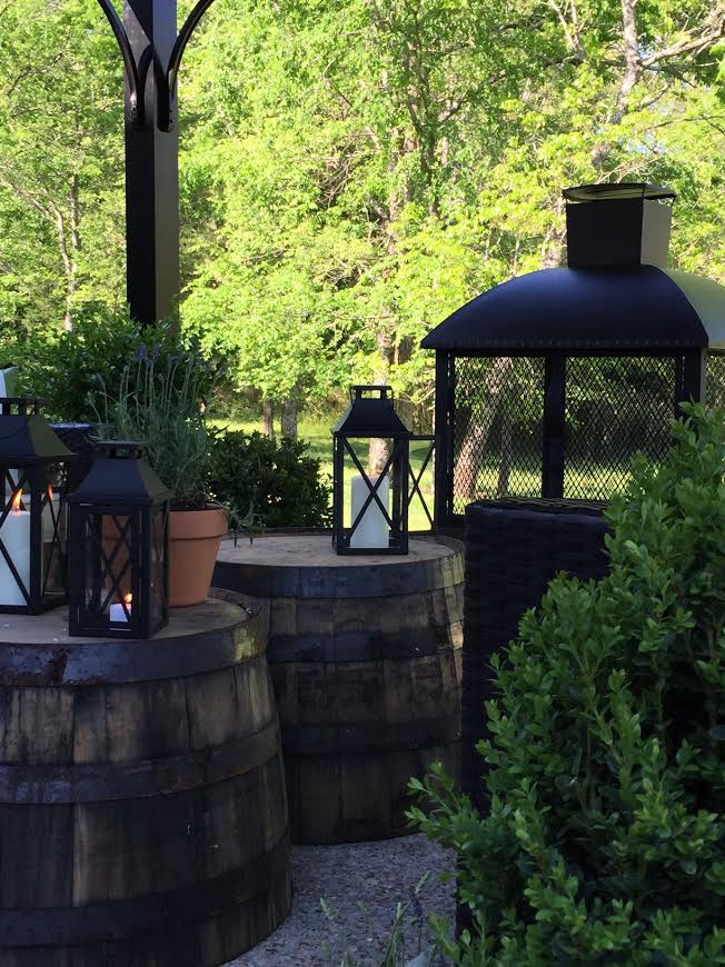 Lanterns and whiskey barrels in outdoor seating area