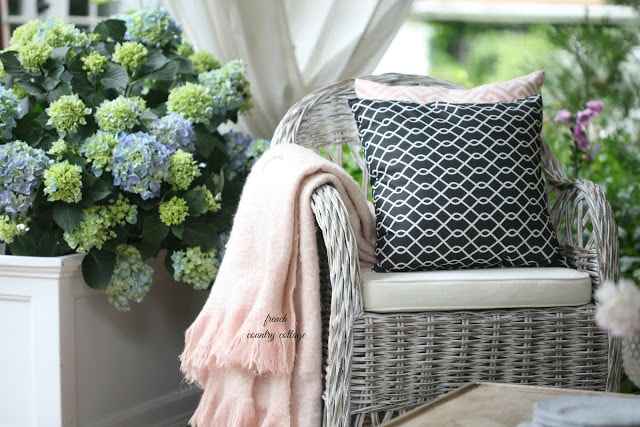 blush throw on wicker chair on patio