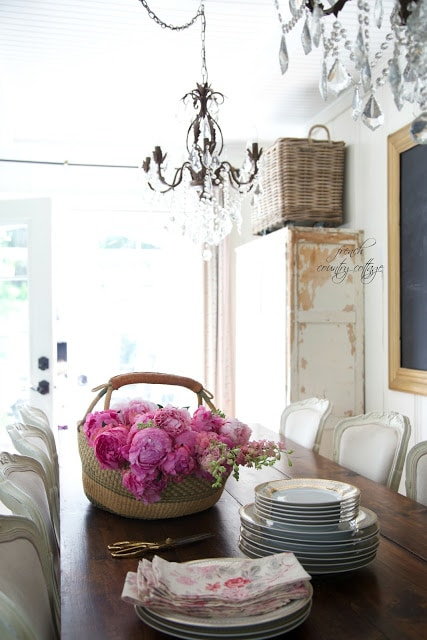 dining room table with basket of peonies and dishes