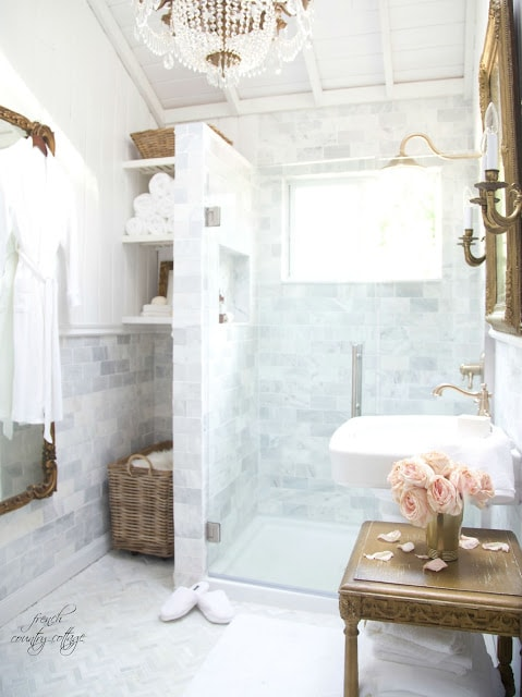 marble bathroom with gold touches and crystal chandelier
