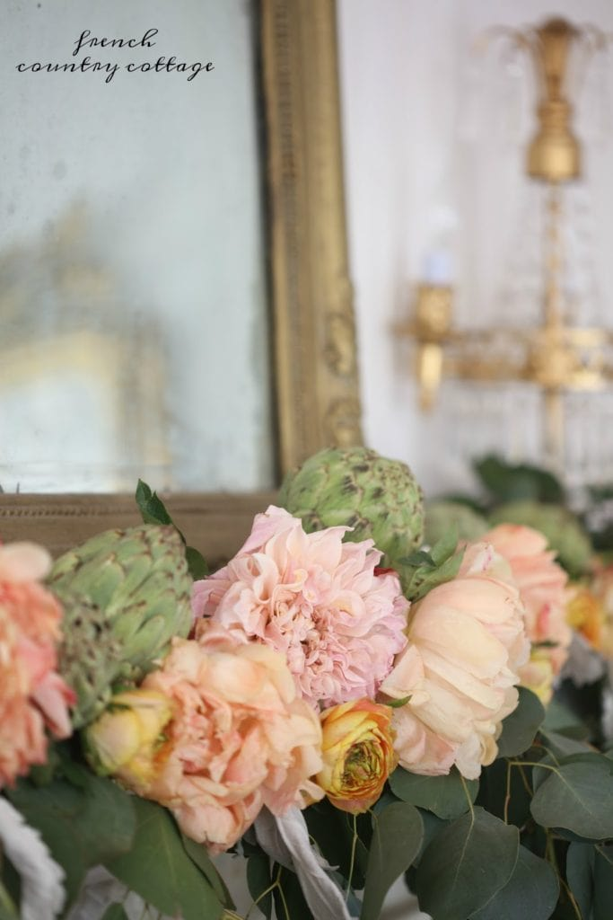 flowers and greens and artichokes for mantel decor