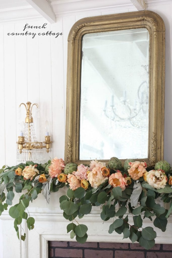 fresh flowers and eucalyptus on a mantel with a vintage mirror and lamp